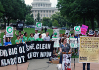Friends of the Earth protests in front of the U.S. Capitol. A woman is at the podium.